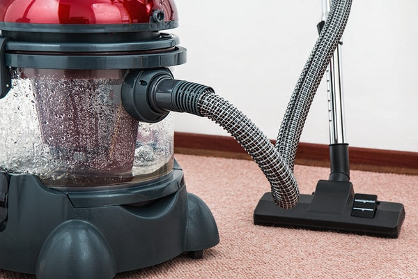 Black and Red canister vaccum cleaner on floor