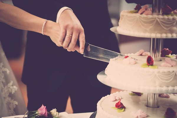 a coupl holding hands and cutting cake